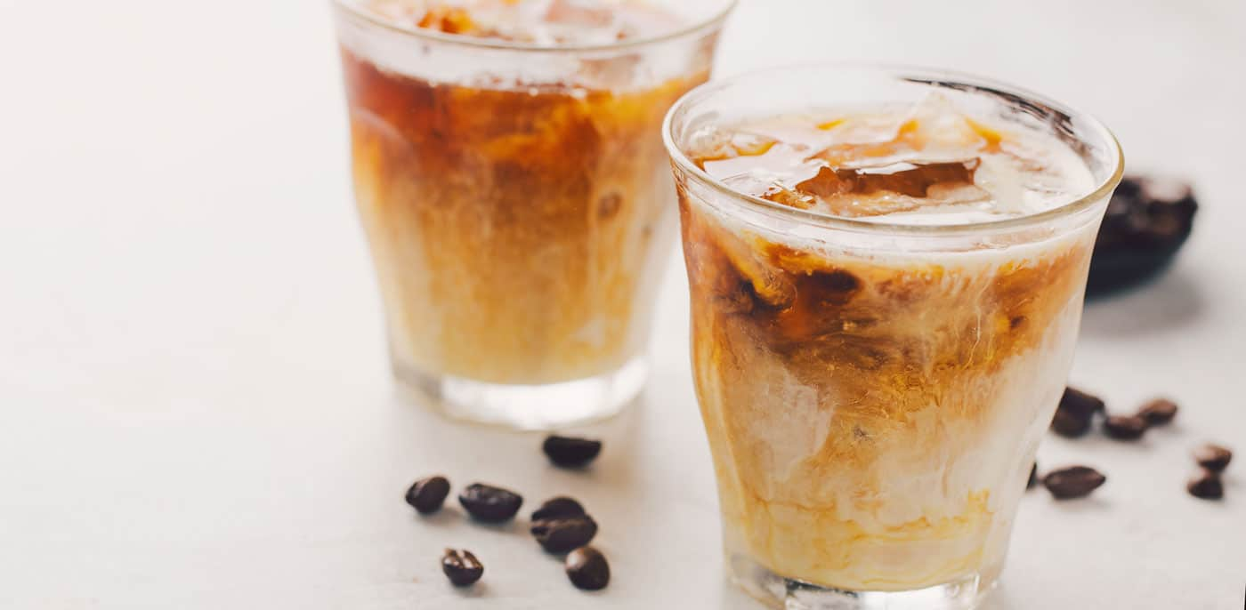 Two glasses of iced coffee with coffee beans scattered nearby