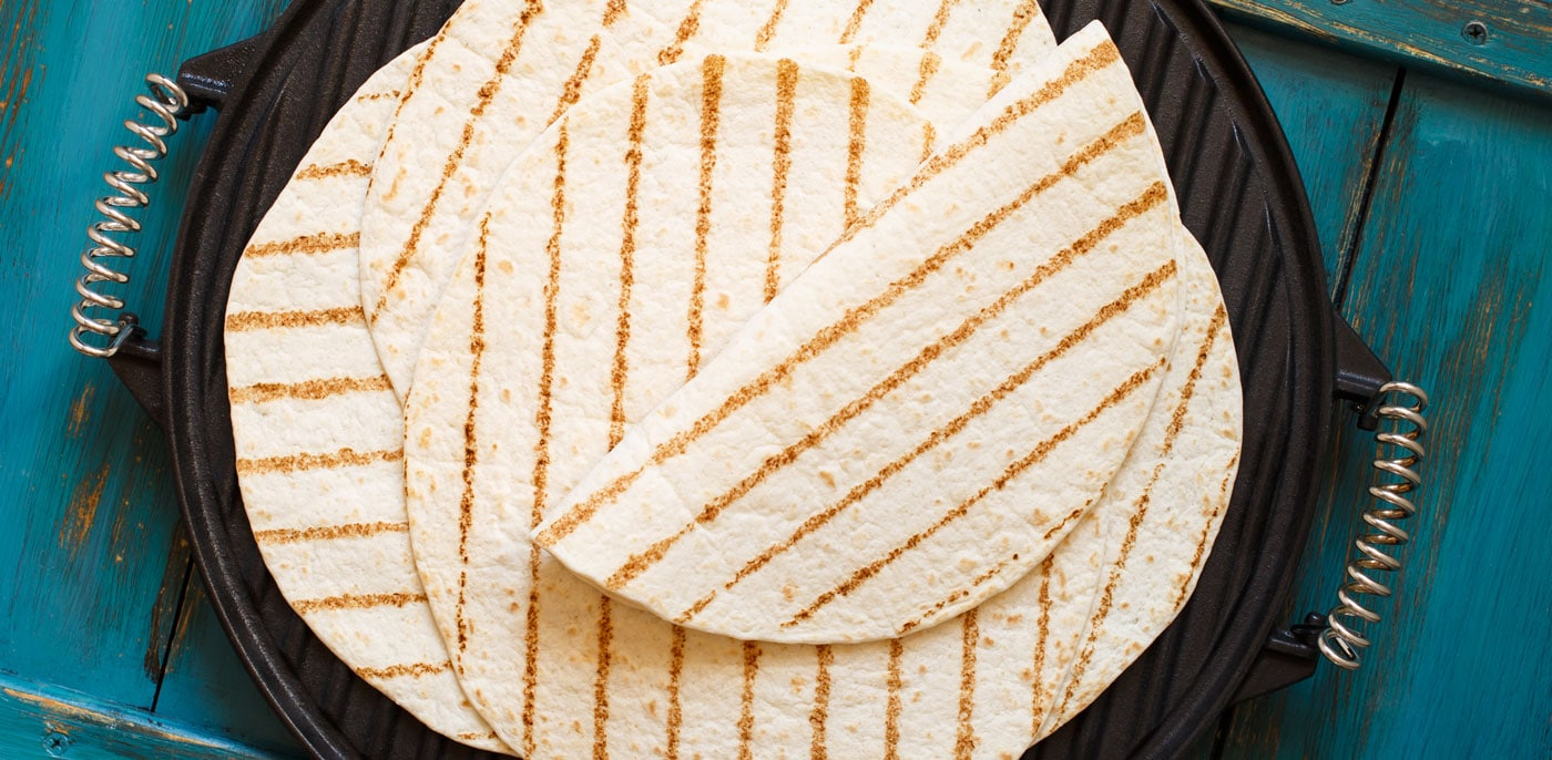 Soft tortillas with grill marks on a cast iron skillet