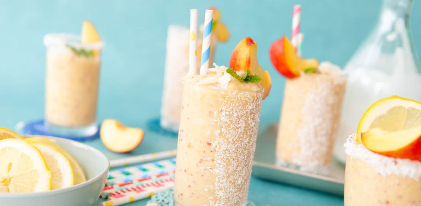 Tropical smoothies with apricot on rim of glass and colorful straws